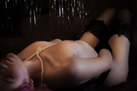 sexy boudoir photo of topless woman wearing pearl necklace and arching her back